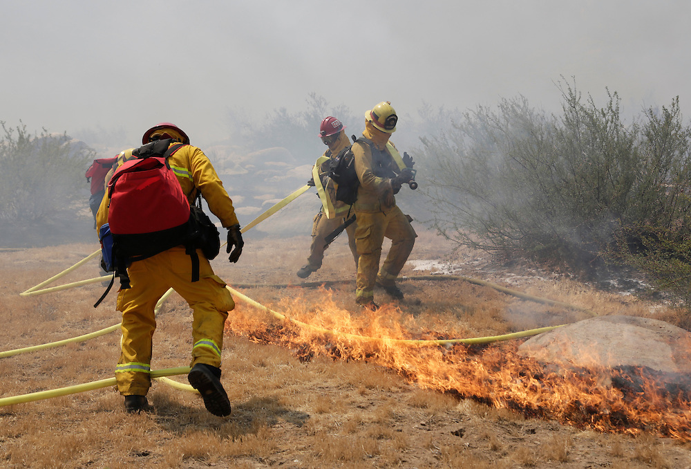 Firefighters rush to move their hose from spreading flames as the Silver Fire burns in the foothills in Cabazon, California August 8, 2013. A wind-whipped California wildfire that doubled in size overnight torched 15 buildings east of Los Angeles, injured at least five people and forced the evacuation of 500 homes in about half a dozen small communities, authorities said on Thursday. REUTERS/Jason Redmond (UNITED STATES - Tags: DISASTER)