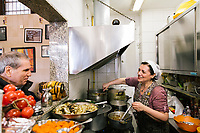 NAPLES, ITALY - APRIL 10th 2018: Owner Marianna Sorrentino prepares pennette with Genovese sauce in the kitchen  while talking to a customer at the Trattoria Malinconico, a popular restaurant in the Vomero district in Naples, Italy, on April 10th 2018.<br /> <br /> Trattoria Malinconico was opened in 1953 by current owner Marianna Sorrentino's parents-in-law. At first it was only a bulk wine cellar, but then he began making a few cooked dishes – small plates that were popular with locals, which eventually morphed into larger meals. Still today the trattoria is frequented the neighborhood's older residents, many of whom have been loyal regulars for years, as well as younger locals and workers, who often stop by for a glass of wine. The menu varies from day to day, and is typically based on traditional Neapolitan recipes. Though some dishes, like meatballs, sausages, and friarielli (rapini, a type of broccoli typical to Naples), are always available.<br />  <br /> <br /> Genovese sauce is a rich, onion-based pasta sauce from the region of Campania, Italy. Likely introduced to Naples from the northern Italian city of Genoa during the Renaissance, it has since become famous in Campania and forgotten elsewhere.<br /> Genovese sauce is prepared by sautéing either beef, veal or pork in a large number of onions, for at least two but as many as ten hours. Large, cylindrical pasta like rigatoni, ziti or candele are favored because they can hold the rich sauce.