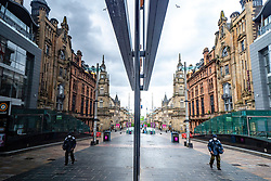 Glasgow, Scotland, UK. 14 May 2020.  With Scotland still in Covid-19 lockdown the city centre of Glasgow remains deserted with with few members of the public on the streets and shops, offices and restaurants closed. Pictured; A virtually deserted Buchanan Street is reflected in a shop window. Iain Masterton/Alamy Live News