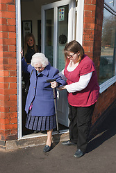 Carer helping old lady down step.