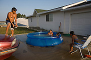 Children keep cool from the summer heat in the newly constructed Heritage Hills housing development in Macy, Nebraska.  From left to right, Christopher Guevara, 11, Alex Guevara, 8, Sharee Jackson, 7, and Ruby Guevara, 4...The 203rd Annual Harvest Celebration hosted by the Umonhon (Omaha) Tribe of Nebraska, held at the Wahnashe' Zhinga Park, in Macy, Nebraska from Aug. 2-5, 2007.  .Images taken for The Kellogg Foundation by Kainaz Amaria © 2007.