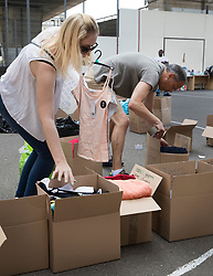 © Licensed to London News Pictures. 18/06/2017. London, UK. Boxes of donated aid are sorted on a basketball court under the A40 flyover by volunteers near site of the burnt out Grenfell tower block . The blaze engulfed the 27-storey building killing dozens - with 34 people still in hospital, many of whom are in critical condition. The fire brigade say that they don't expect to find anyone else alive. Photo credit: Peter Macdiarmid/LNP