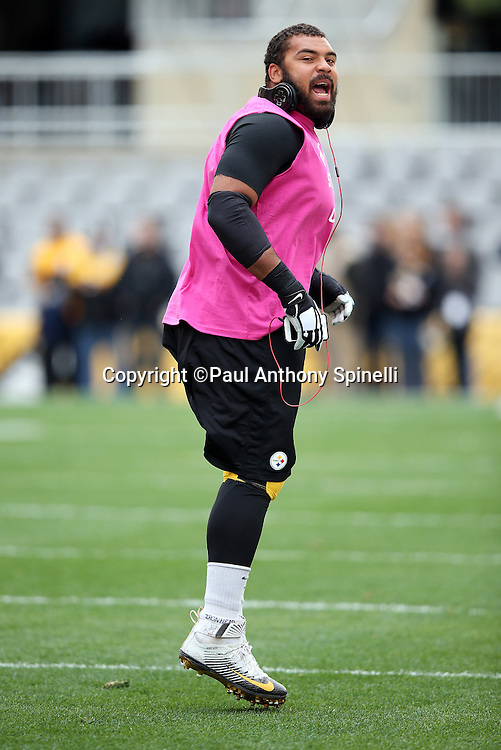 """Pittsburgh Steelers defensive end Cameron Heyward (97) calls out while warming up during pregame while wearing a pink top in memory of his father, former New Orleans Saints running back Craig """"Ironhead"""" Heyward who died of brain cancer, before the 2015 NFL week 6 regular season football game against the Arizona Cardinals on Sunday, Oct. 18, 2015 in Pittsburgh. The Steelers won the game 25-13. (©Paul Anthony Spinelli)"""