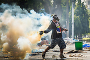 02 DECEMBER 2013 - BANGKOK, THAILAND:  An anti-government rioter throws a tear gas grenade back at police during riots in Bangkok Monday. Anti-government protestors and Thai police continued to face off Monday for a second day. Police used tear gas, water cannons and rubber bullets against protestors who charged their positions near the barriers on Chamai Maruchet bridge on Phitsanulok Road, which leads to the Government House.    PHOTO BY JACK KURTZ