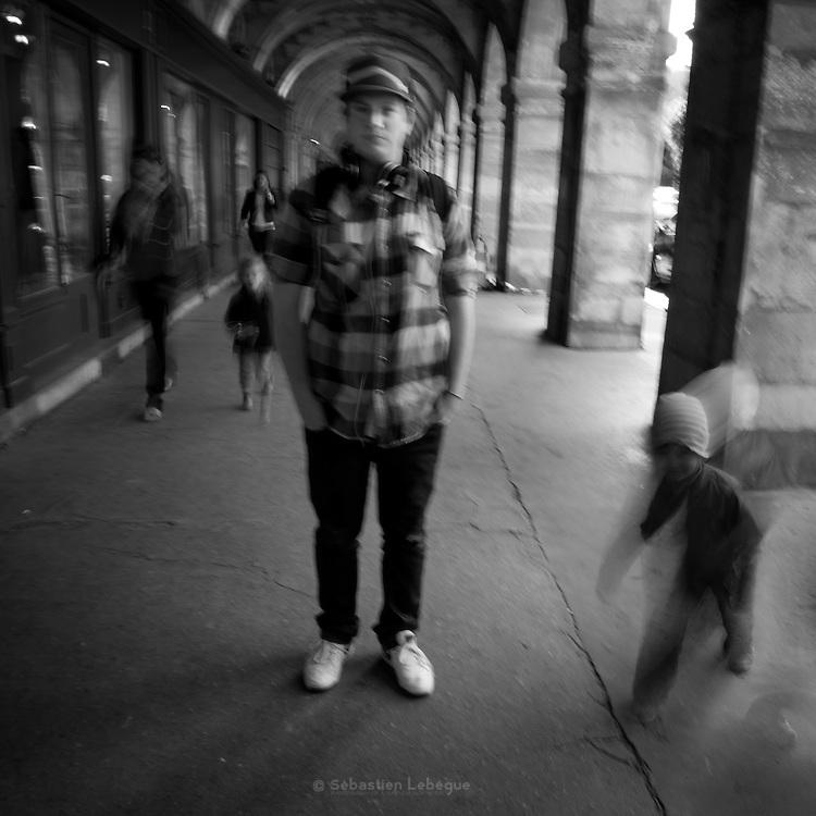 Paris - Place des Vosges - Juin 2012 - Jeune homme à la chemise à carreau. Un enfant court en premier plan.