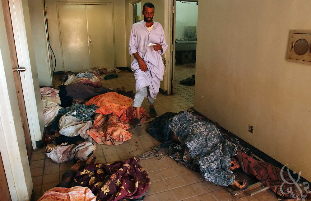 An Iraqi man walks past bodies in an overflow morgue area at the Najaf hospital on August 30, 2003, following yesterday's massive car bombing at the nearby Imam Ali shrine that killed one of the most important Shiite clerics in Iraq, Mohammed Baqir al-Hakim and more than 100 others.