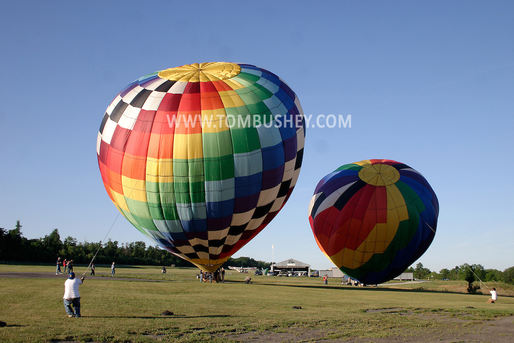 Workers hold down balloons with ropes as the balloons are filled with hot air at Randall Airport in Middletown, N.Y. July 2, 2005.