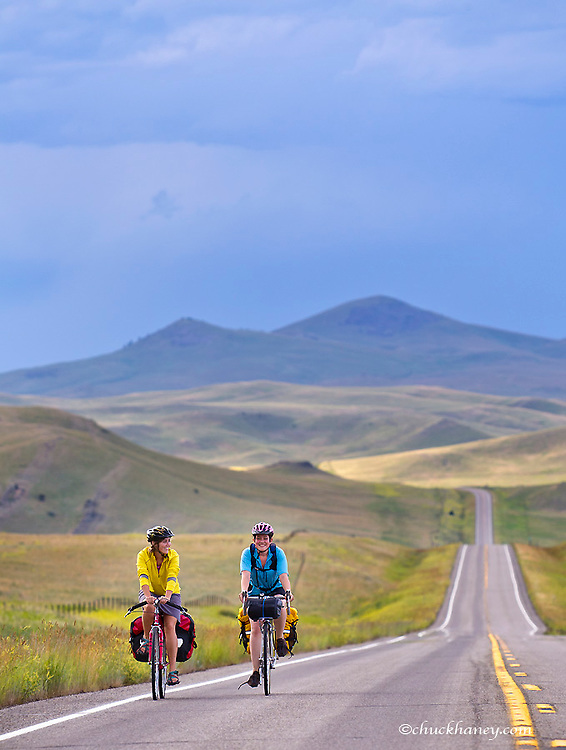 Bicycle touring on a stormy afternoon on Highway 287 near Wolf Creek, Montana, USA model released