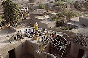 The Natomo family poses for a portrait with all of their possessions on the roof of their home in Kouakourou, Mali. Standing, wearing yellow, is Soumana's father. The Natomo family lives in two mud brick houses in the village of Kouakourou, Mali, on the banks of the Niger River. They are grain traders and own a mango orchard. According to tradition Soumana is allowed to take up to four wives; he has two.  From Peter Menzel's Material World Project that showed 30 statistically average families in 30 countries with all of their possessions.