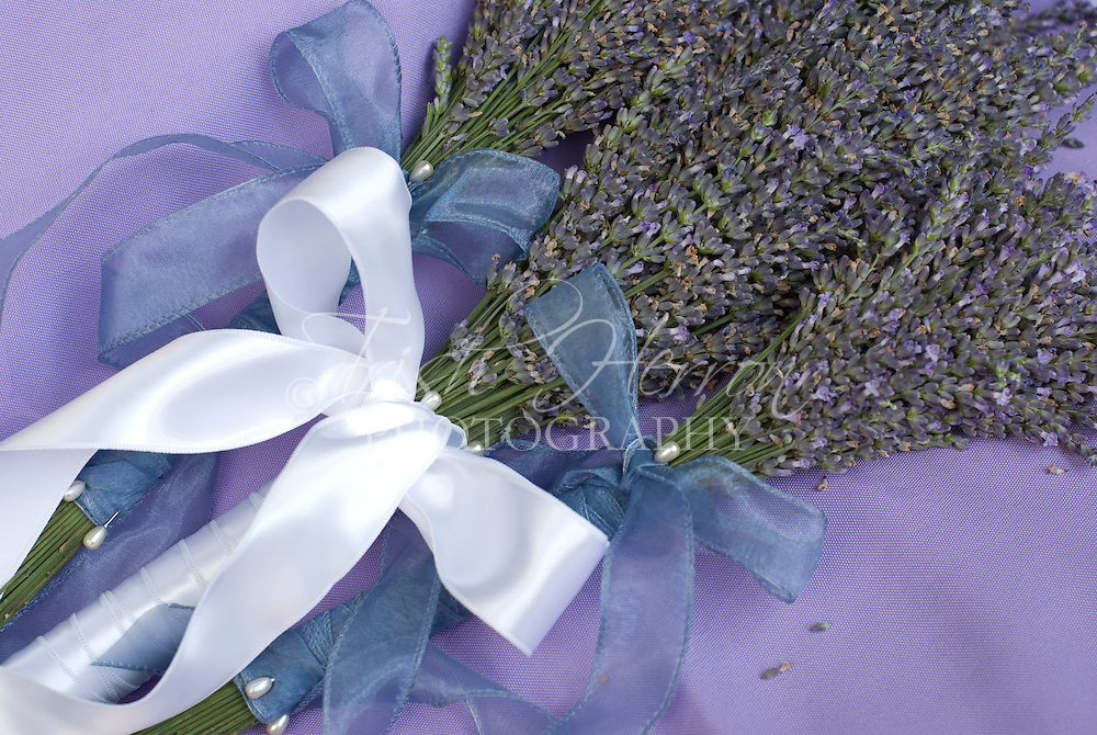 One bridal bouquet with two small bouquets, all of fresh lavendar with white satin and blue mesh bows.