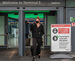 © Licensed to London News Pictures. 24/07/2020. London, UK. A young women wears a mask at Terminal 5, London Heathrow as face masks become compulsory today in airports, shops, takeaway cafes and supermarkets and enforced by the Police, with anyone who fails to wear one liable to a £100 fine. Photo credit: Alex Lentati/LNP