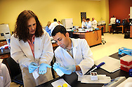 Rowan-Cabarrus Community College students participate in a genetics lab at RCCC's NC Research Campus location. They are isolating various food items in order to determine whether they contain genetically modified organisms. This is instructor Carol Scherczinger, PhD (at left) with a student.