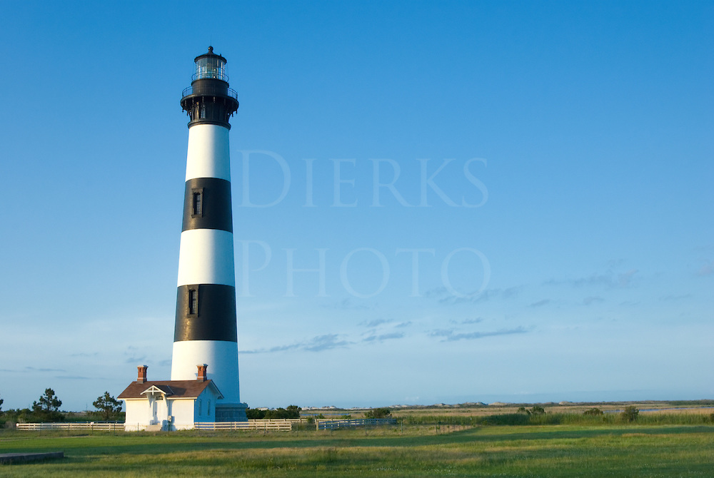 Black and white striped lighthouse in open landscape in evening light, Bodie Island in the Outer Banks, Nags Head, North Carolina, USA.