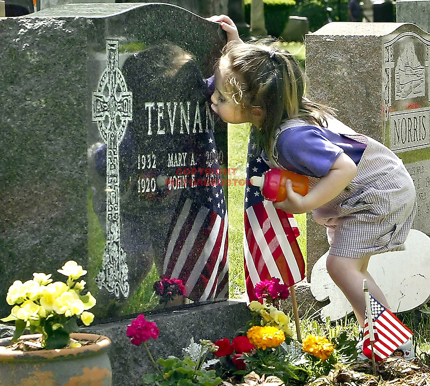 Mary Ellen Tevnan kisses the grave of her grandparents at Cedar Grove Cemetery during Memorial Day ceremony.