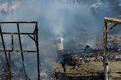 October 26, 2016 - Calais, France - A migrant runs between burned down huts in the Calais Jungle, on October 26, 2016. Huge fires destroyed a mayor part of the refugee camp today. (Credit Image: © Markus Heine/NurPhoto via ZUMA Press)