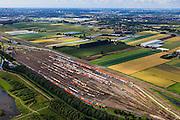 Nederland, Zuid-Holland, Zwijndrecht, 15-07-2012; Kijfhoek, rangeerterrein voor goederentreinen. Overzicht van de verdeelsporen met linksboven in beeld de railremmen. .Kijfhoek huisvest Keyrail, exploitant Betuweroute en is in beheer bij ProRail. De Betuweroute, die begint als Havenspoorlijn op de Maasvlakte, verbindt via Kijfhoek de Rotterdamse haven met het achterland. Het rangeeremplacement dient voor het sorteren van goederenwagons waarbij gebruik gemaakt wordt van de zwaartekracht, het 'heuvelen': de wagons worden de heuvel opgeduwd, bij het de heuvel afrollen komen ze, door middel van wissels, op verschillende verdeelsporen. Railremmen zorgen voor het automatisch remmen van de wagons. Na het heuvelproces staan de nieuw samengestelde treinen op aparte opstelsporen..Kijfhoek, railway yard used by ProRail and Keyrail (Betuweroute operator). Kijfhoek connects via the Betuweroute (beginning as Havenspoorlijn on the Maasvlakte), through the port of Rotterdam with the hinterland. The shunting yard for sorting wagons makes use of gravity. The new trains are assembled on separate tracks..luchtfoto (toeslag), aerial photo (additional fee required).foto/photo Siebe Swart