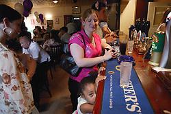Guests standing at bar at wedding reception,