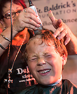 Joel Hernandez, 7, of Arcadia, reacts as he has his head-shaving during the annual St. Baldrick's Day head-shaving fundraiser on Thursday, March 14, 2013, in Arcadia, California. More than100 women and men shaved their heads to raises money for child cancer research. The event, ``St. Baldrick's Day,'' is part of a global effort and the world's biggest volunteer-driven fundraising program for childhood cancer. (Photo by Ringo Chiu/PHOTOFORMULA.com).