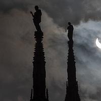 Milan, Italy - 20 March 2015: Partial solar eclipse seen through the steeples of Duomo di Milano