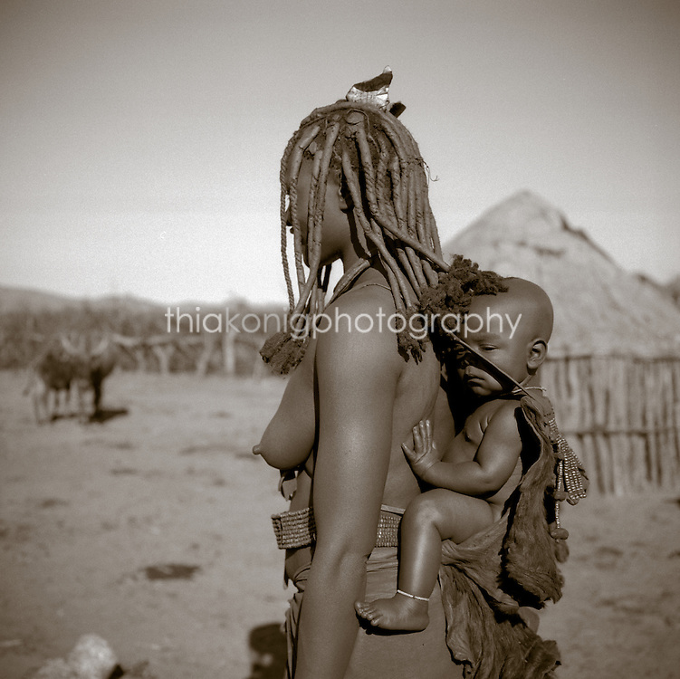Side view of an Akha woman carrying a baby on her back, village hut in background, Northern Namibia, Africa.