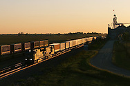 The last light of the day reflecting off its flanks, a Union Pacific intermodal train makes its way toward Chicago, passing the giant grain elevator at Flagg, IL, just outside of Rochelle.