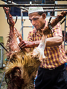 24 SEPTEMBER 2015 - BANGKOK, THAILAND:  A man butchers a ritualistically sacrificed sheep during the celebration of Eid al-Adha at Haroon Mosque in Bangkok. Eid al-Adha is also called the Feast of Sacrifice, the Greater Eid or Baqar-Eid. It is the second of two religious holidays celebrated by Muslims worldwide each year. It honors the willingness of Abraham to sacrifice his son, as an act of submission to God's command. Goats, sheep and cows are sacrificed in a ritualistic manner after services in the mosque. The meat from the sacrificed animal is supposed to be divided into three parts. The family retains one third of the share; another third is given to relatives, friends and neighbors; and the remaining third is given to the poor and needy.    PHOTO BY JACK KURTZ