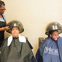 Michelle Munn styles the hair of Lenore Slade, left, and Liana Slade, 13, at Munn's B Shoppe in Leland, N.C.