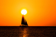 Sail captured touching sun as it does into ocean.