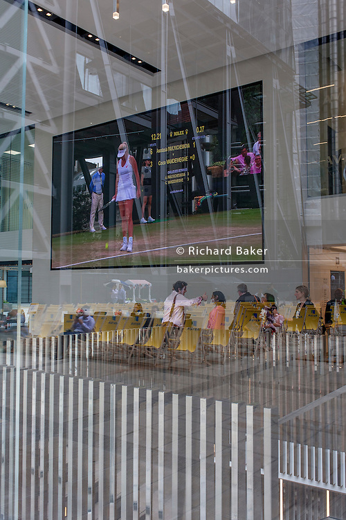 City workers watch a womens' tennis match on a huge screen outside the City of London headquarters of insurance company Aviva during Wimbledon fortnight, on 4th July, London, United Kingdom. Seen through the large window of Aviva's foyer, reflections of City buildings as well as visitors to the building merge with the tennis action. (Photo by Richard Baker / In Pictures via Getty Images)