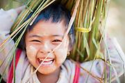 Smiley little girl carrying harvest overhead (Myanmar)
