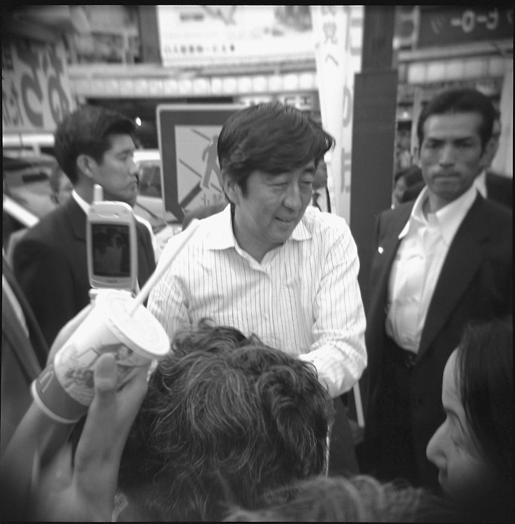 """Shinzo Abe greets supporters at tokyo rally endorsing Local candidates for Office in the General election called by Korizumi's push to reform the Postal service.....An October 2005 government reshuffle saw him appointed as chief cabinet secretary, a key position sometimes referred to as the """"prime minister's wife"""".....His promotion was seen as a sign that Prime Minister Junichiro Koizumi may want Mr Abe to succeed him next Year,  when he is expected to step down."""
