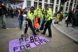 © Licensed to London News Pictures. 08/10/2019. London, UK. Extinction Rebellion activists being arrested outside DEFRA in Westminster. Activists have converged on Westminster for a second day, blockading roads in the area and calling on government departments to 'Tell the Truth' about what they are doing to tackle the Emergency. Photo credit: Ben Cawthra/LNP