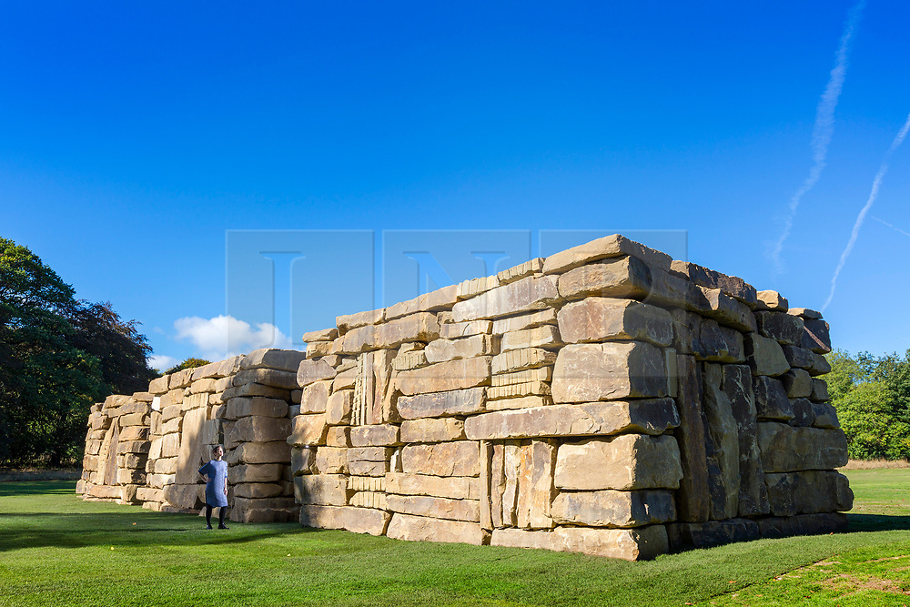 © Licensed to London News Pictures. 27/09/2018. Wakefield UK. Kerry Chase looks at a Sean Scully sculpture called Wall Dale Cubed, the massive sculpture made of Yorkshire stone measures 4mx28mx6m. Yorkshire Sculpture Park has unveiled a major new exhibition called Inside Outside & is the work of Sean Scully. The exhibition is the first by the Irish-born artist in the UK & is made up of Sculptures & paintings by Scully. The exhibition runs from the 29th of September until the 6th January. Photo credit: Andrew McCaren/LNP