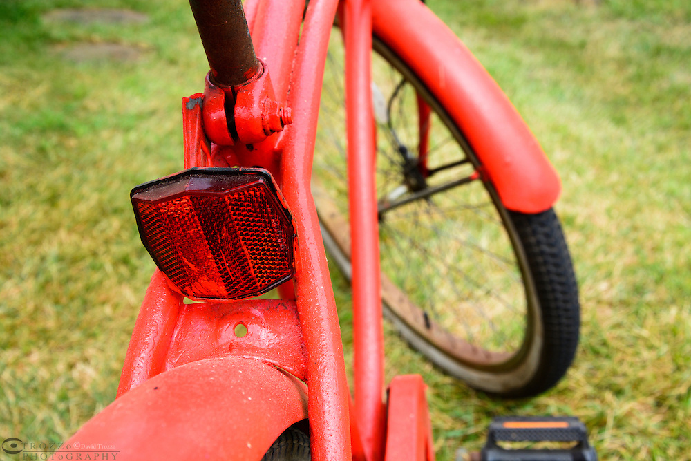 Close up of a classic single speed bicycle and safety reflector.