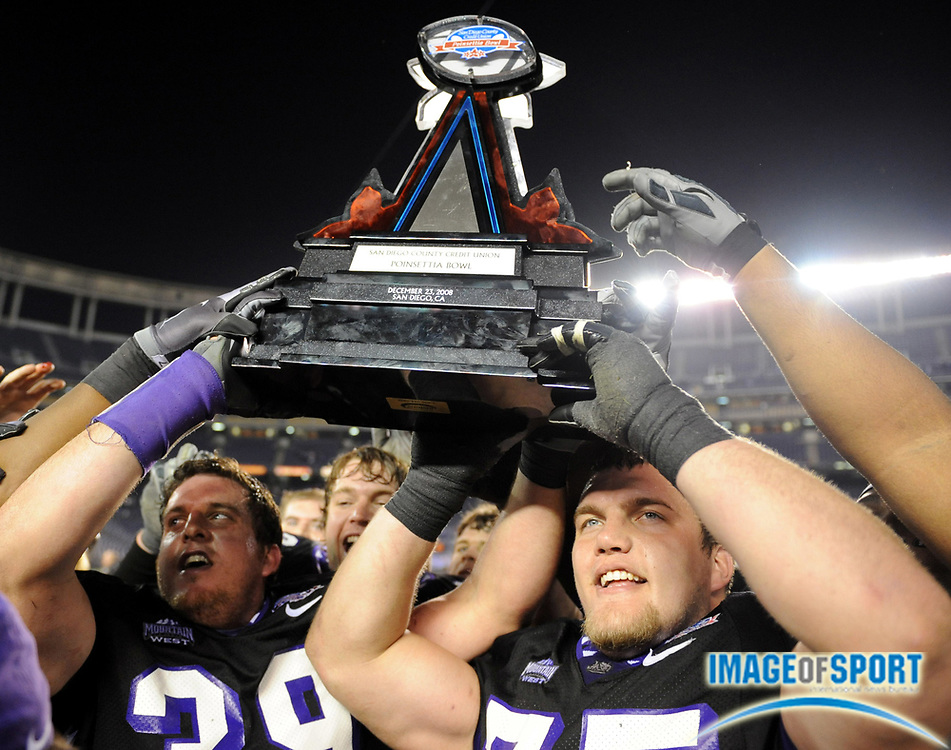 Dec 23, 2008; San Diego, CA, USA; Texas Christian Horned Frogs linebacker Jason Phillips (39), left, and center Blake Schulueter (75) hoist the championship trophy after the Horned Frogs' 17-16 victory over the Boise State Broncos in the Poinsettia Bowl at Qualcomm Stadium.
