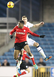 Barnsley's Kelvin Etuhu battles for the ball with Millwall's Mark Beevers - Photo mandatory by-line: Robin White/JMP - Tel: Mobile: 07966 386802 23/11/2013 - SPORT - Football - Millwall - The Den - Millwall v Barnsley - Sky Bet Championship