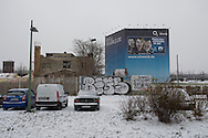 A building covered in advertising standing on a snow-covered section of former no-mans land along the route of the former Berlin Wall near Warschauerstrasse in former East Berlin. The route of the Wall, which stood from 1962-1989, has been developed into the 'Mauerweg,' a thoroughfare which traces most of the route of the Wall which encircled the city and divided it into East and West Berlin during the Cold War. In the years following the 1989 civil uprising in the German Democratic.Republic, most of the Wall was removed as part of the reunification strategy which united the pro-Soviet DDR and the Federal Republic of (West) Germany.