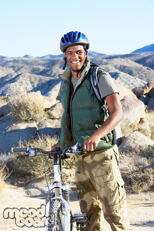 Young man standing with mountain bike in front of hills