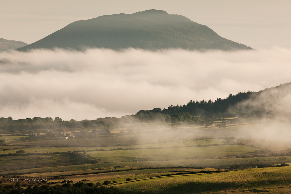 Huge banks of sea fog swirled in off the Irish Sea, isolating hill summits almost creating islands within the hilly landscape. The iron-age hill fort of Carn Fadryn sits atop the peak in the distance, a large settlement of almost 100 circular huts.