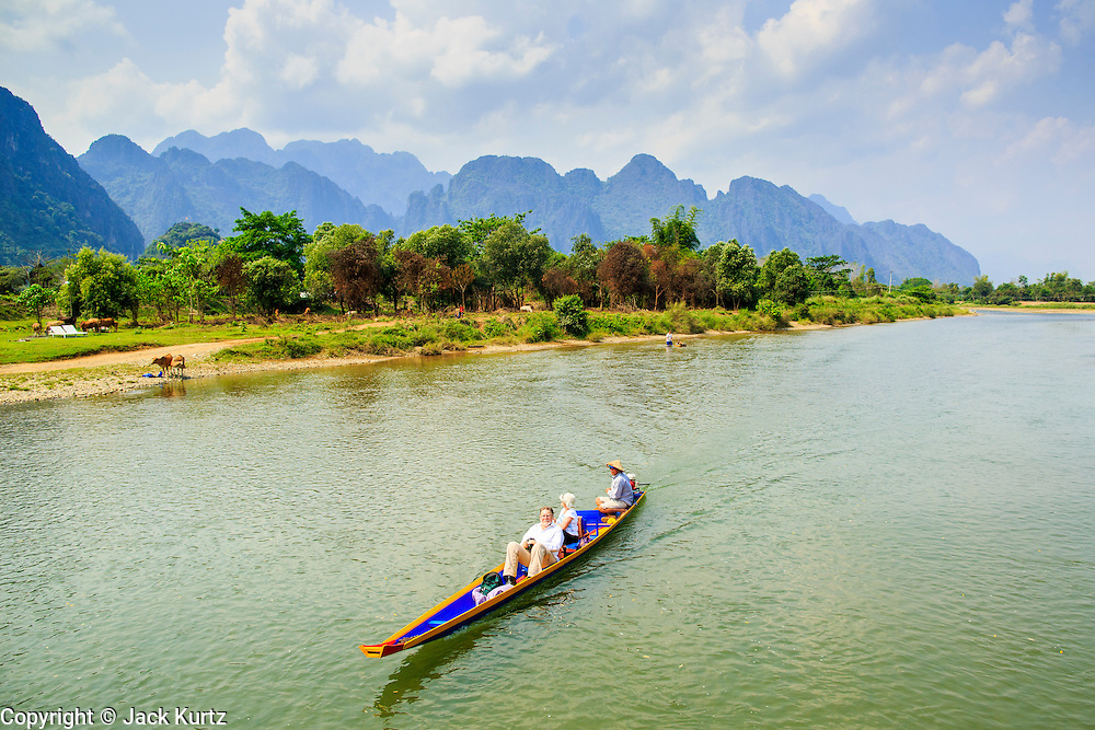 09 MARCH 2013 - VANG VIENG, LAOS:  Tourists are motored down the Nam Song River in Vang Vieng, Laos. Vang Vieng is a stop on the highway between Vientianne and Luang Prabang and is most famous for kayaking and tubing and the limestone karsts that dot the area. PHOTO BY JACK KURTZ