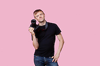 Portrait of a happy young male photographer holding camera over pink background