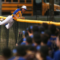 Tupelo first baseman Hunter Elliott leaps onto the top of the right field fence trying to chase down a foul ball in hops for catch it for an out against Oxford Tuesday night.