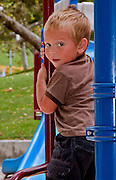 Young Boy climbing On The Playground Equipment