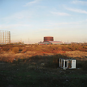 Victorian Gasometers and modern industrial sheds tower over wasteland and dumped portaloo. Beckton, East London. 12.2003 UK