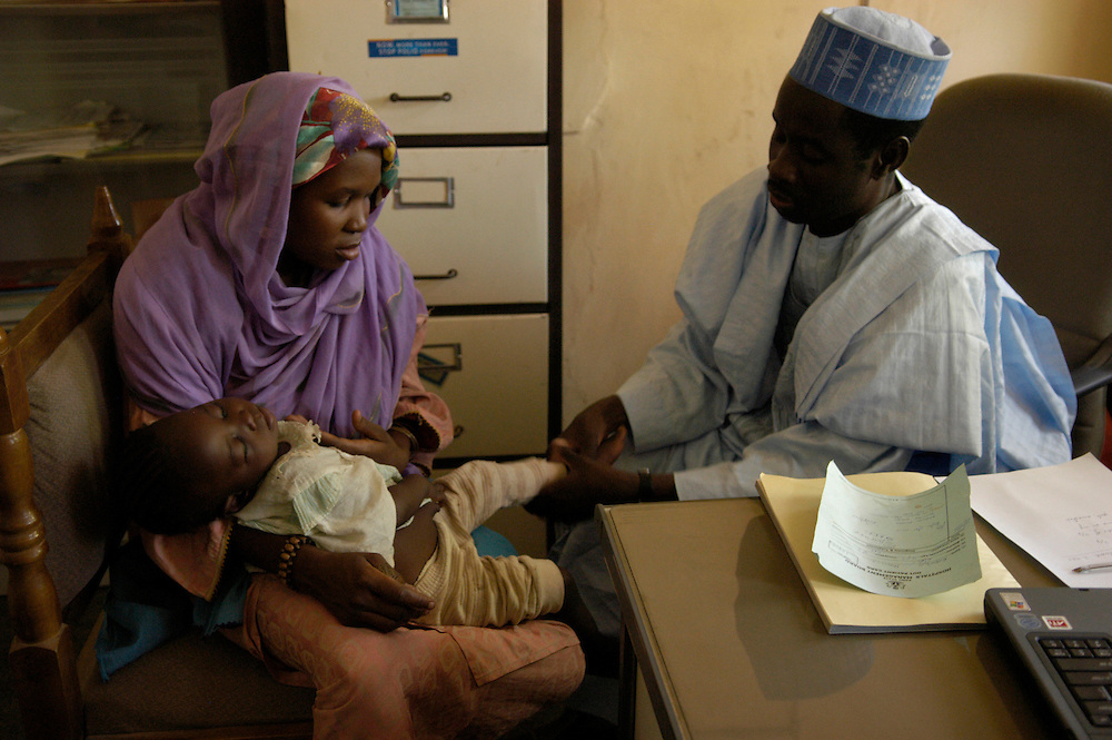 Dr. Ali Guda Takai examines the legs of 20-month-old Nusaiba Haruna at the polio surveillance clinic at the Infectious Disease Hospital in Kano. The girl's mother, Hadiza, told the doctor that her three older children were fully immunized, but since Nusaiba was born, no vaccinators had come to their home.