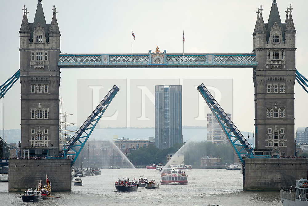 © Licensed to London News Pictures. 09/09/2015. London, UK. British royal rowbarge Gloriana leading the flotilla as it passes underneath the raised bridge at Tower Bridge. . A Royal River Salute takes place at Tower Bridge in London to mark the Queen becoming the longest reigning monarch in British history. The Queen will have reigned for 63 years and seven months , passing the record set by her great-great-grandmother Queen Victoria. Photo credit: Ben Cawthra/LNP