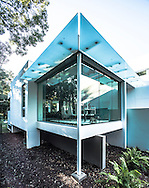 Cantilevered dining room with 1 inch tick glass panels and glass sunscreens.