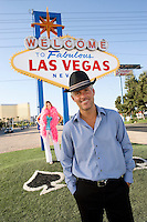 Portrait of mid-adult man in front of Welcome to Las Vegas sign, mid-adult woman behind.