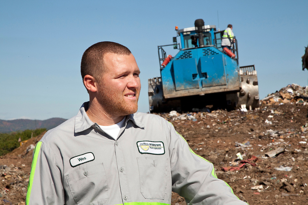 Male Employee in front of earth moving tractor in open cell of sanitary landfill