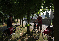 Tourists from Germany enjoy a Boat and Bike tour through Flanders. Tour members stop at an historic church in Damme, Belgium, on Sunday, July 11, 2010. (Photo © Jock Fistick)